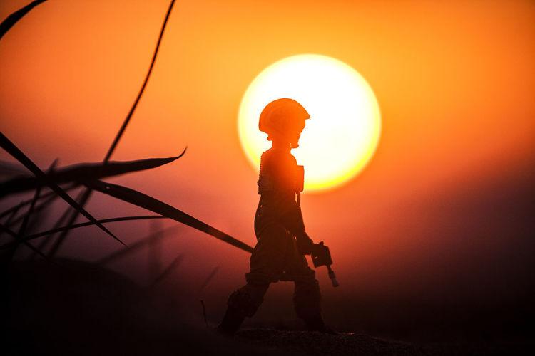 Back Lit Full Length Leisure Activity Lens Flare Lifestyles Men Nature Orange Color Outdoors Person Rear View Silhouette Sky Standing Sun Sunlight Sunset