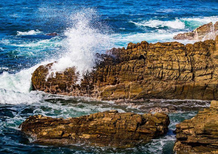 Scenic view of sea waves splashing on rocks