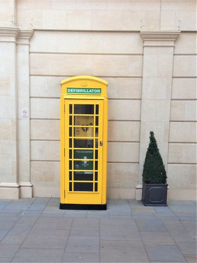 First Aid Architecture Building Exterior Built Structure Communication Connection Day Defibrillator Footpath Glass - Material Green Color No People Outdoors Technology Telecommunications Equipment Telephone Telephone Booth Text Transparent Wall - Building Feature Western Script Yellow
