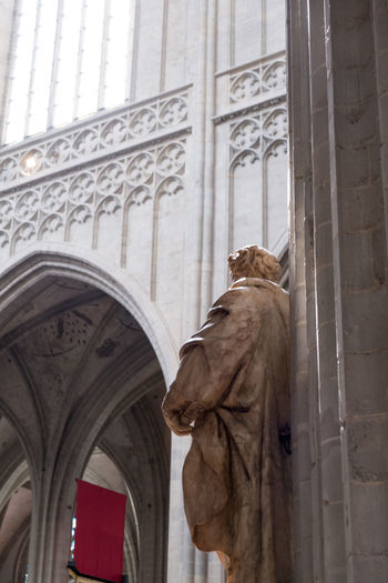 Statue of a saint inside a gothic cathedral in Europe. Pointed arches and groin vault decorated with delicate tracery. Interior of 14th century European cathedral. Antwerp Antwerp, Belgium Antwerpen Antwerpen Centraal Antwerpen, Belgium Antwerp Belgium Architectural Column Architecture Art And Craft Building Exterior Built Structure Creativity Day History Human Representation Low Angle View Male Likeness No People Outdoors Place Of Worship Religion Sculpture Spirituality Statue