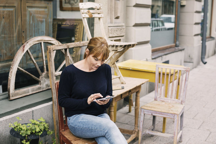 Full length of woman using mobile phone while sitting on seat