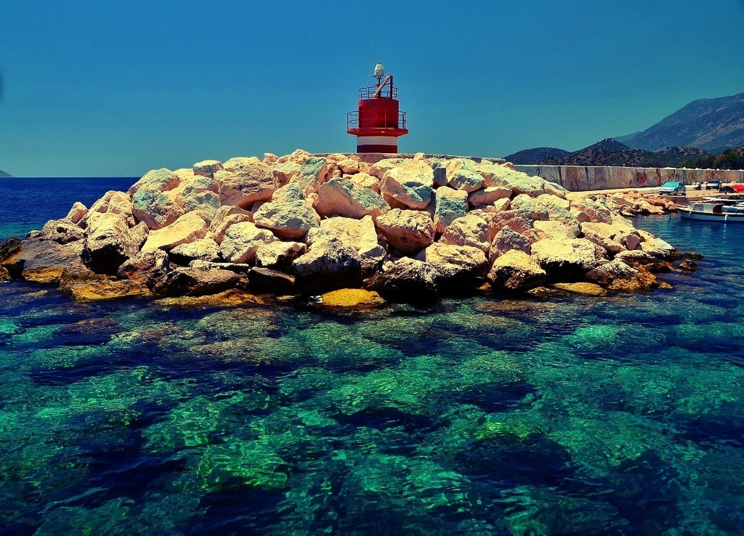 water, sea, clear sky, rock - object, blue, rock, rock formation, lighthouse, tranquility, tranquil scene, built structure, mountain, nature, scenics, architecture, guidance, building exterior, beauty in nature, horizon over water, day
