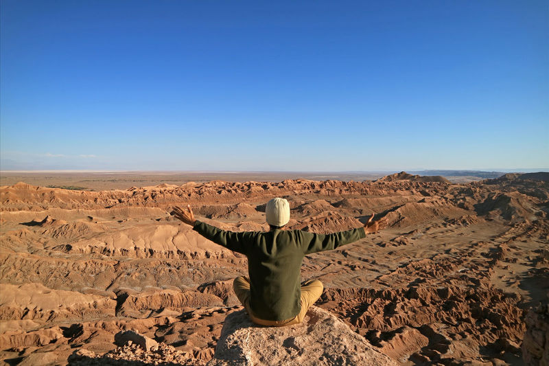 Rear view of man walking in desert against clear sky