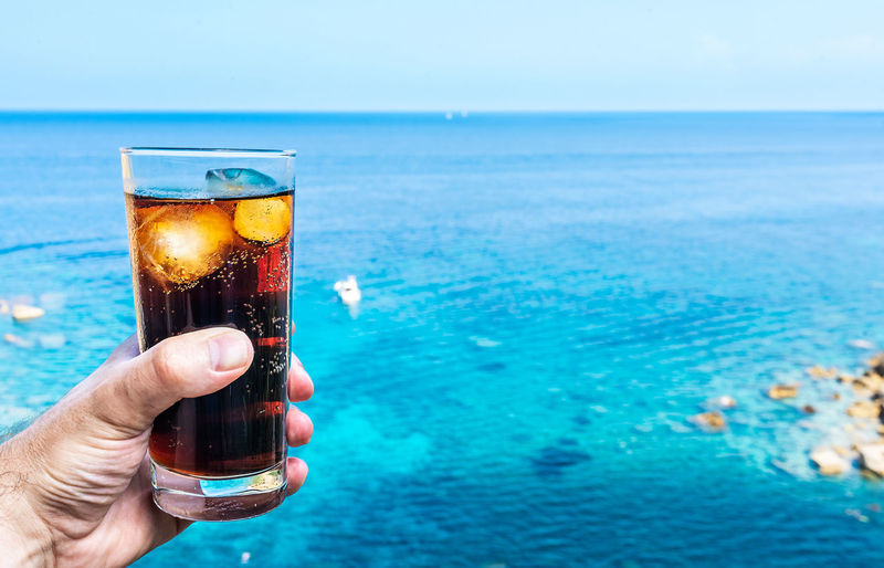Beverage Carbonated Ice Cube Sunny Cola Drink Drinking Drinking Glass Food And Drink Glass Hand Holding Horizon Horizon Over Water Human Body Part Human Hand Lifestyles One Person Outdoors Refreshment Sea Sky Soft Drink Summer Water