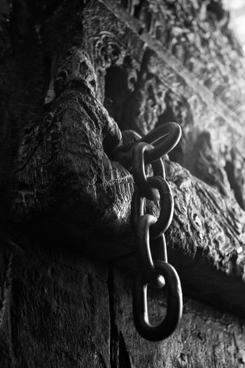A chain hangs off an ancient carved wooden door at a temple in Ayutthaya, Thailand Ancient Ayutthaya Check This Out Chedi Close-up Focus On Foreground Gable Metal Monastic Monochrome Ormament Outdoors Pagoda Ruin Ruined Sight Site Teak Temple Thai Thailand Travel Wat White Wood