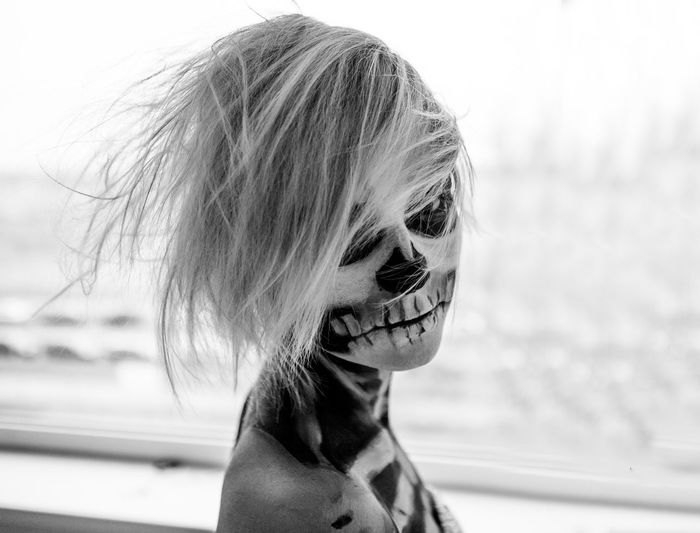 Close-up portrait of a girl in skeleton body paint