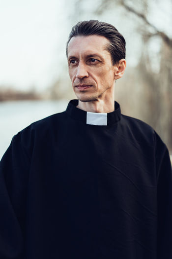 Handsome catholic priest portrait with collar Pastor Priest Collar Religion Religious  Belief Saint Father Beliver Man Men People person One Person Caucasian Middle Ages Catholicism Catholic Christianity Christian Faith Portrait Focus On Foreground Standing Waist Up Adult Real People Looking Away Day Lifestyles Looking Young Adult Front View Serious Clothing Young Men Outdoors Contemplation