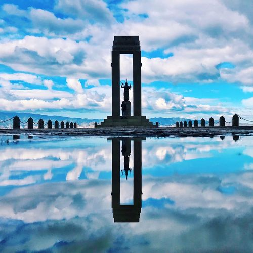 Reflection of tower on water in city against sky
