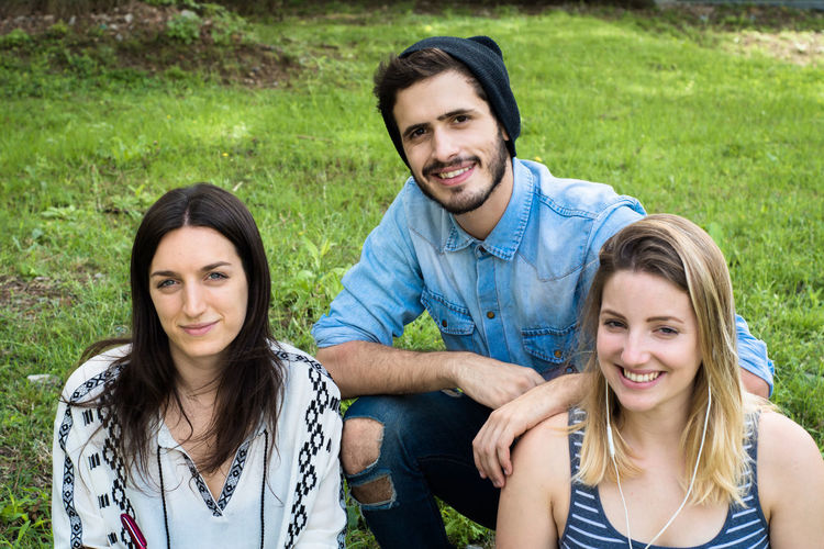 Portrait of smiling friends sitting on grass