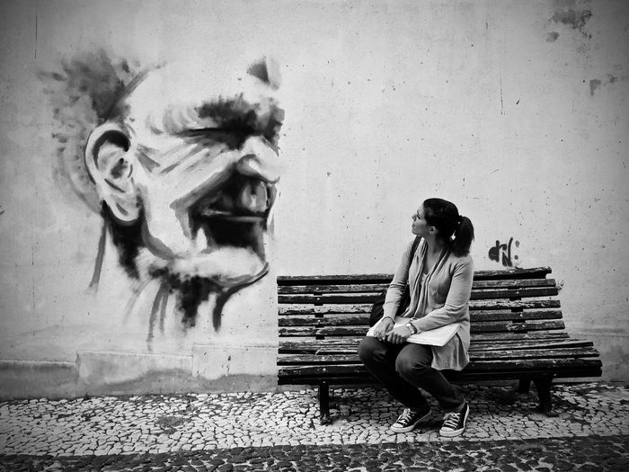 Full Length Of Woman Sitting On Bench While Looking At Painting On Wall