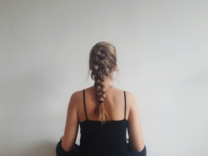 Woman with braided hair standing against wall