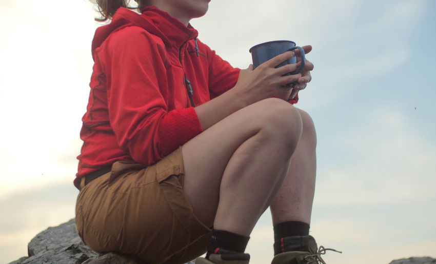 caucasian female hiker sitting on a rocky peak next to a backpack drinking beverage out of a mug Alpine Backpacking Boots Camping Expedition Freedom Hiking Nature Sitting Travel Trekking Woman Active Adventure Backpack Casual Clothing Child Clothing Day Female Focus On Foreground Food And Drink Full Length Hairstyle Hobby Holding Leisure Activity Lifestyles Low Angle View Mountain Nature One Person Outdoors Peak People person Real People Red Sitting Sky Trek Women