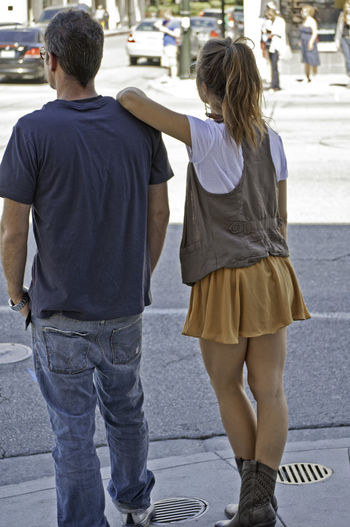 Rear view of man and woman standing on street