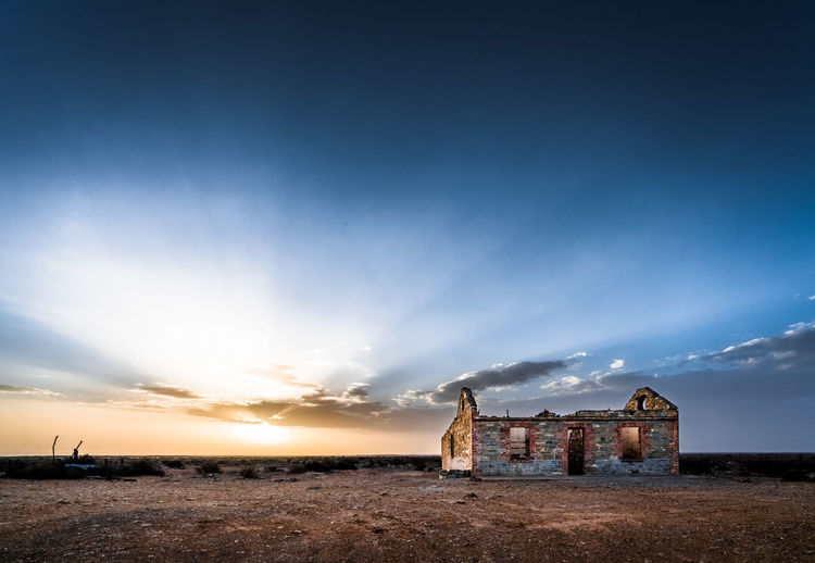 Old abandoned building on land against sky during sunset
