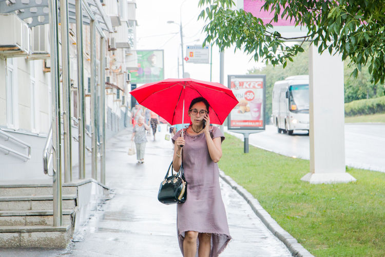 In the rain Adult Beautiful Woman Day Front View Holding Lifestyles One Person Outdoors Plant Protection Rain Real People Security Standing Three Quarter Length Umbrella Wet Women Young Adult Young Women