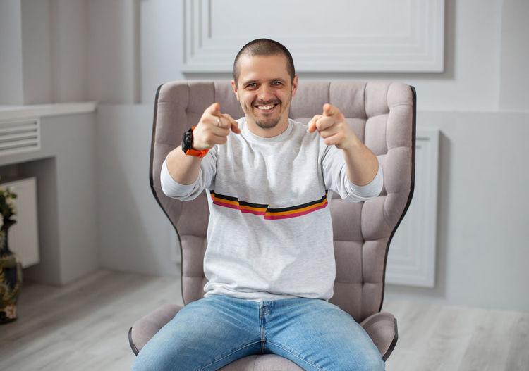 Smiling man pointing on camera sitting in modern interiour on chair One Person Smiling Front View Looking At Camera Portrait Indoors  Sitting Happiness Three Quarter Length Emotion Gesturing Lifestyles Casual Clothing Domestic Life Human Body Part Furniture Domestic Room Living Room Human Arm Human Limb Arms Raised Jeans