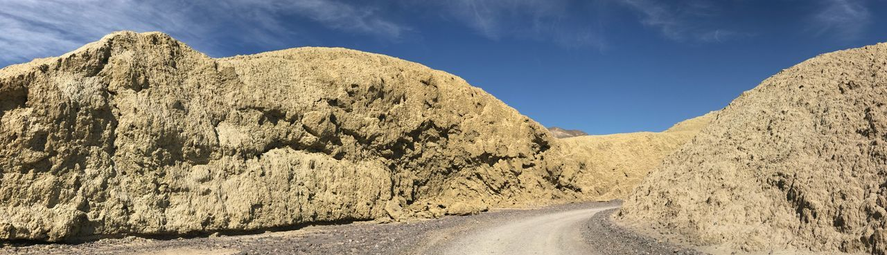 Panoramic view of road amidst rocks against sky