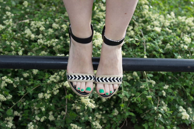 Low Section Of Woman Wearing Sandal On Railing Over Field