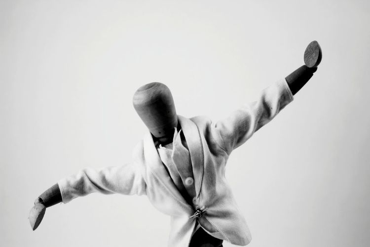 Rear view of man with arms raised against white background