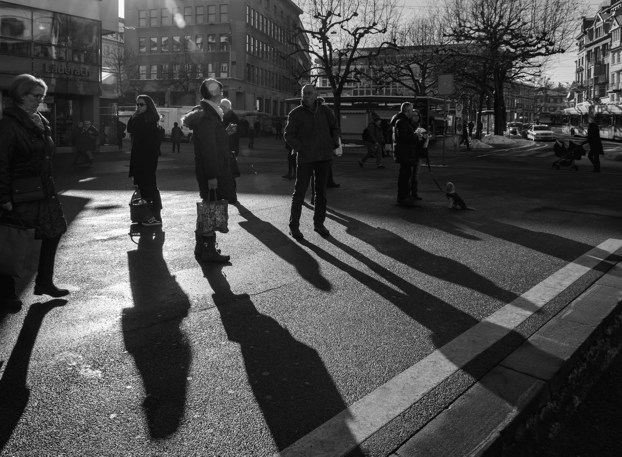 real people, building exterior, city life, built structure, city, architecture, men, shadow, tree, walking, women, outdoors, lifestyles, sunlight, day, large group of people, adult, people, adults only