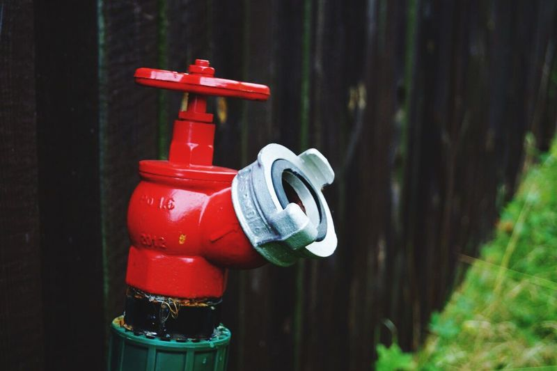 Close-up of red fire hydrant against wooden fence