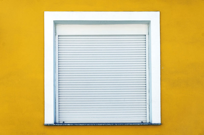 Close-up of closed window on yellow wall