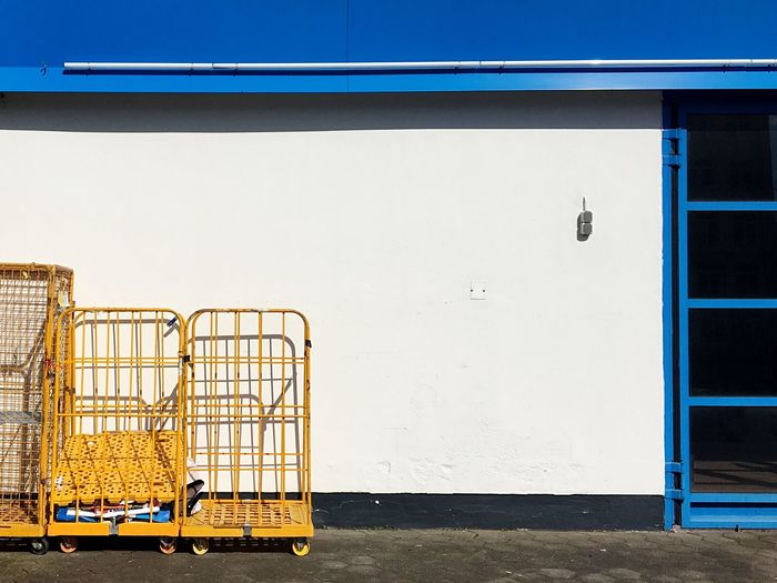 Yellow metal cart structure against white wall