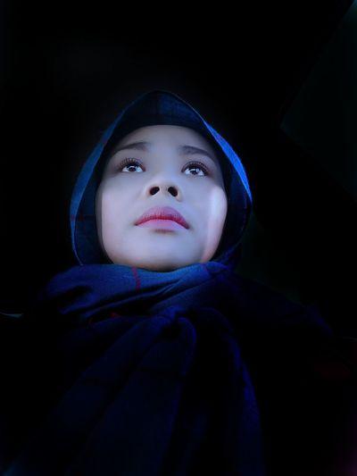 Low angle view of woman wearing hijab looking away in darkroom