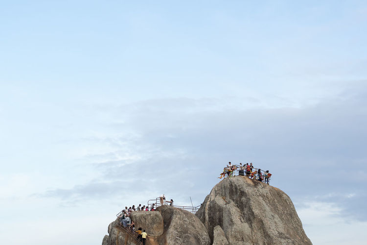People on rock against cloudy sky