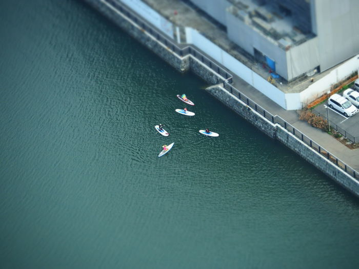 Aerial view of people paddleboarding on river