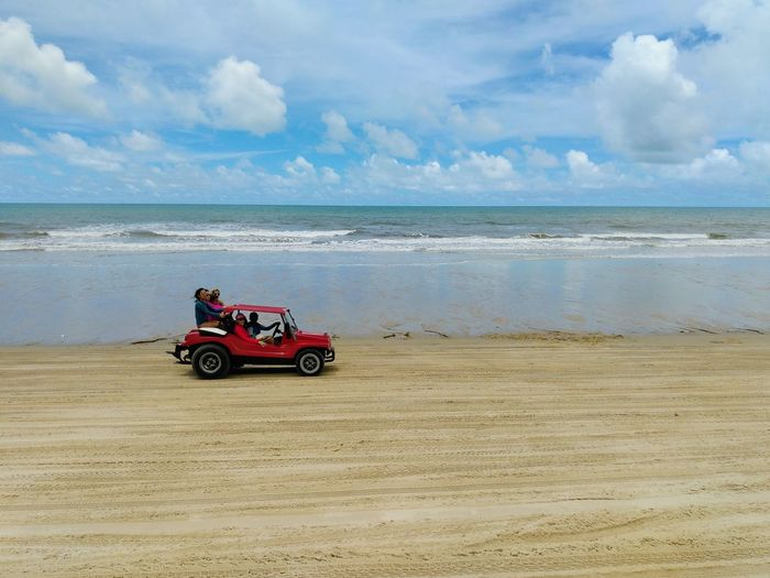 a red car rides on the sand along the beach Buggy Sea Water Beach Sand Sky Horizon Over Water Cloud - Sky Sand Dune Off-road Vehicle 4x4 Low Tide Desert Arid Climate Barren Tire Track