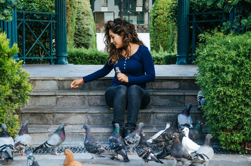 Full length of young woman feeding pigeons while sitting on steps