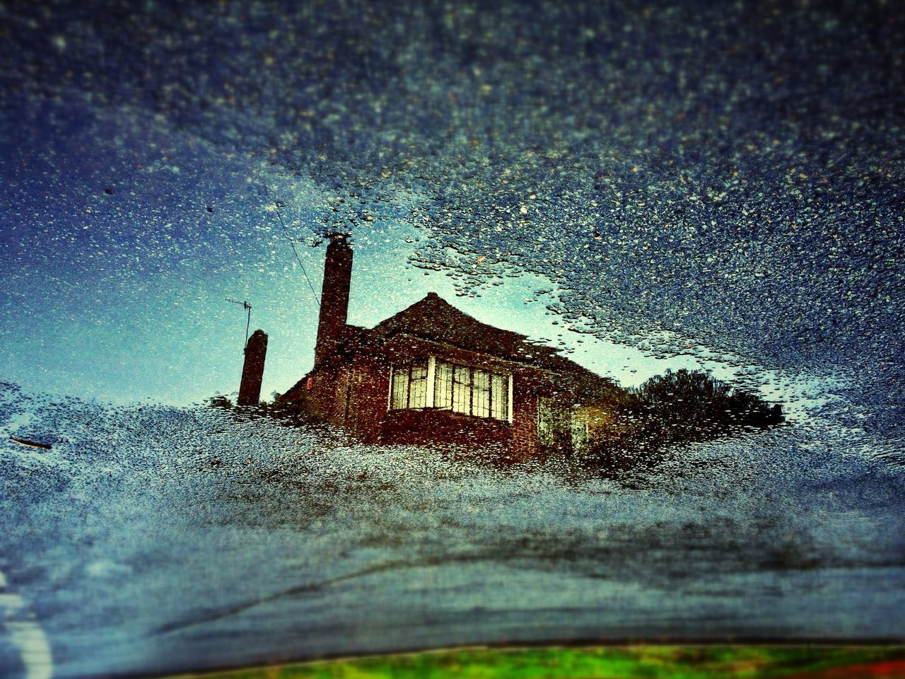 Reflection of built structure in puddle