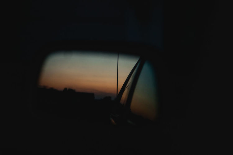 Reflection of silhouette car on side-view mirror at sunset