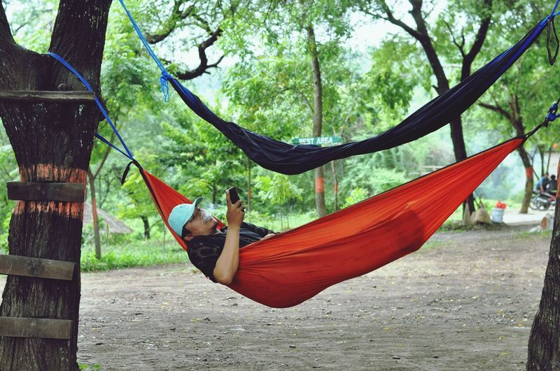 Man using mobile phone while relaxing in hammock