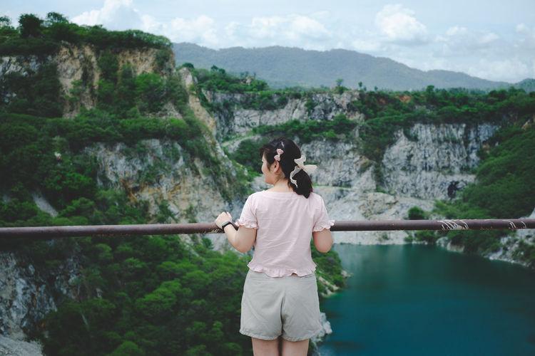 Rear view of woman looking at mountains, landmark of pattaya, thailand.