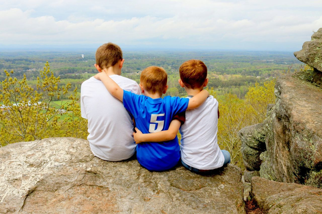 Rear view of three friends sitting on top of cliff