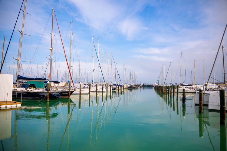 Water Nautical Vessel Transportation Sailboat Mode Of Transportation Sky Reflection Moored Pole Mast Cloud - Sky Harbor No People Tranquility Nature Waterfront Sea Tranquil Scene Scenics - Nature Outdoors Marina Yacht Port Turquoise Colored
