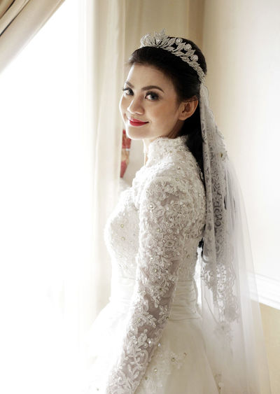 Portrait of woman in wedding dress standing against window