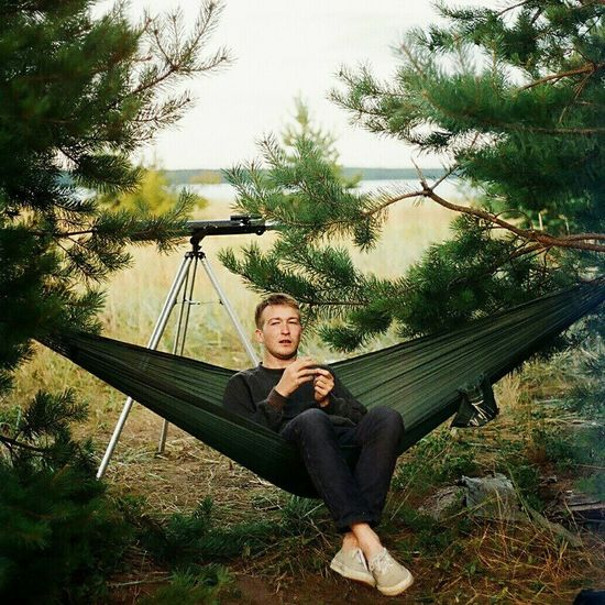 Portrait Of Young Man Relaxing On Hammock