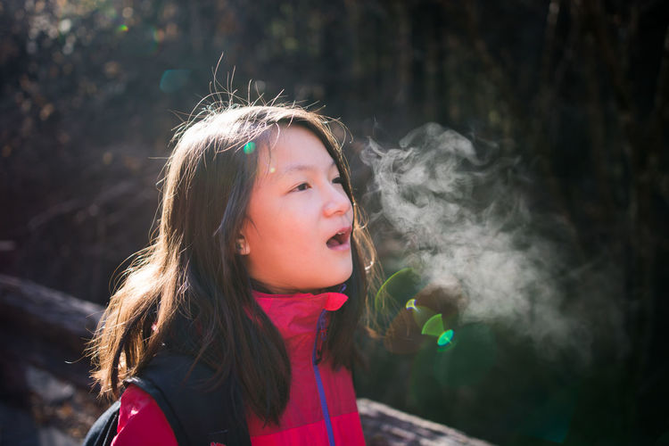 Girl breathing out fog to test cold temperature at roadside. Breath Hair Shiny Smoke Sunlight Winter Cold Exhale Face Flare Fog Girl Jungle Outdoor Red Cloth Roadside