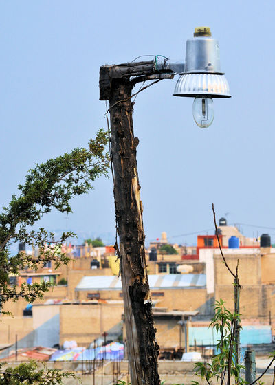 Interesting lamp post being used in a small neighborhood in Mexico Lamp Post Light Mexico Architecture Building Exterior Built Structure City Clear Sky Day Low Tech Nature Neighborhood No People Outdoors Residential Building Sky Tree Wooden Post