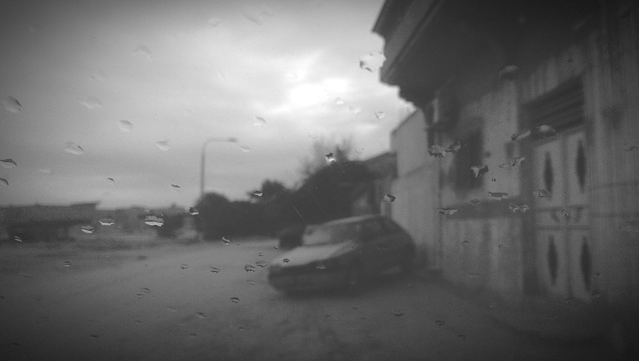 window, rain, wet, weather, drop, raindrop, sky, car, indoors, land vehicle, water, looking through window, built structure, road, no people, architecture, city, day, building exterior, close-up