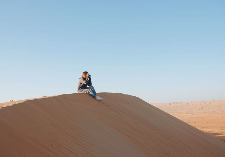 Desert Sand Dune Clear Sky Sand Lifestyles Leisure Activity Outdoors One Person Nature Sky Adventure Landscape Young Adult Wanderlust Taking Photos Photography Photographer Woman Sitting Alone Oman Wadi