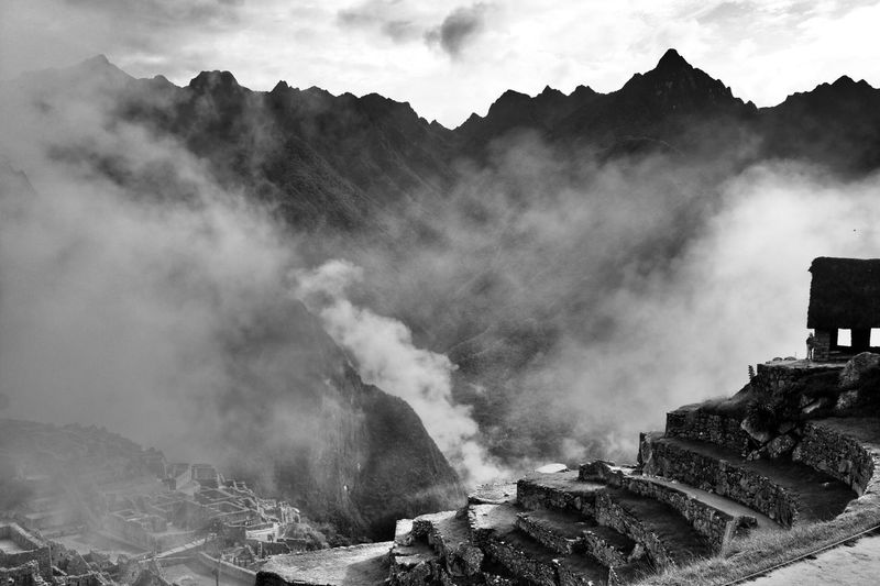 Machu picchu by mountains during foggy weather