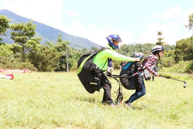 Couple Paragliding On Grassy Field Against Clear Sky