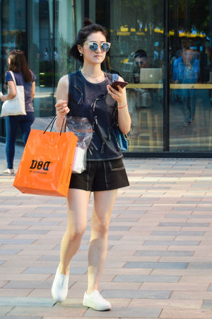 Beautiful Woman City Consumerism Day Fashion Full Length Lifestyles Mobile Phone One Person Outdoors People Real People Retail  Smiling Sunglasses Using Phone Wireless Technology Young Adult Young Women