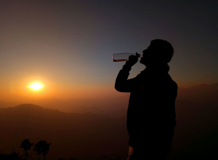 Drink and a beautiful sunset is all we need! Bhimtal, Uttarakhand Travel Photography Beauty In Nature Holding Incredible India Leisure Activity Lifestyles Mobile Phone Mountain Nature One Person Photographer Photographing Photography Themes Portable Information Device Real People Scenic Landscapes Selfie Silhouette Sky Standing Sun Sunrise Sunset Technology