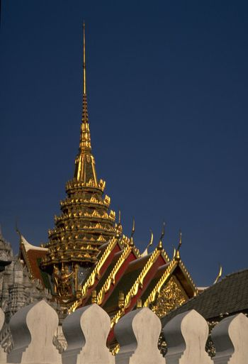 The Grand Palace in Bangkok is actually a collection of buildings in a walled complex. including Wat Phra Kaew (Temple of the Emerald Buddha). One of Thailand's most famous tourist attractions is also the Thai King's home, houses the Royal court and is the administrative seat of government. http://pics.travelnotes.org 43 Golden Moments Architecture ASIA Bangkok Blue Capital Cities  Clear Sky Detail Famous Place Neighborhood MapGraphic Michel Guntern No People Palace Place Of Worship Religion Sky Temple Thailand Tourism Travel Travel Destinations Travel Photography Travel Photos Travel Pics