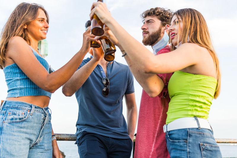 Friendships holding beer bottle against sky